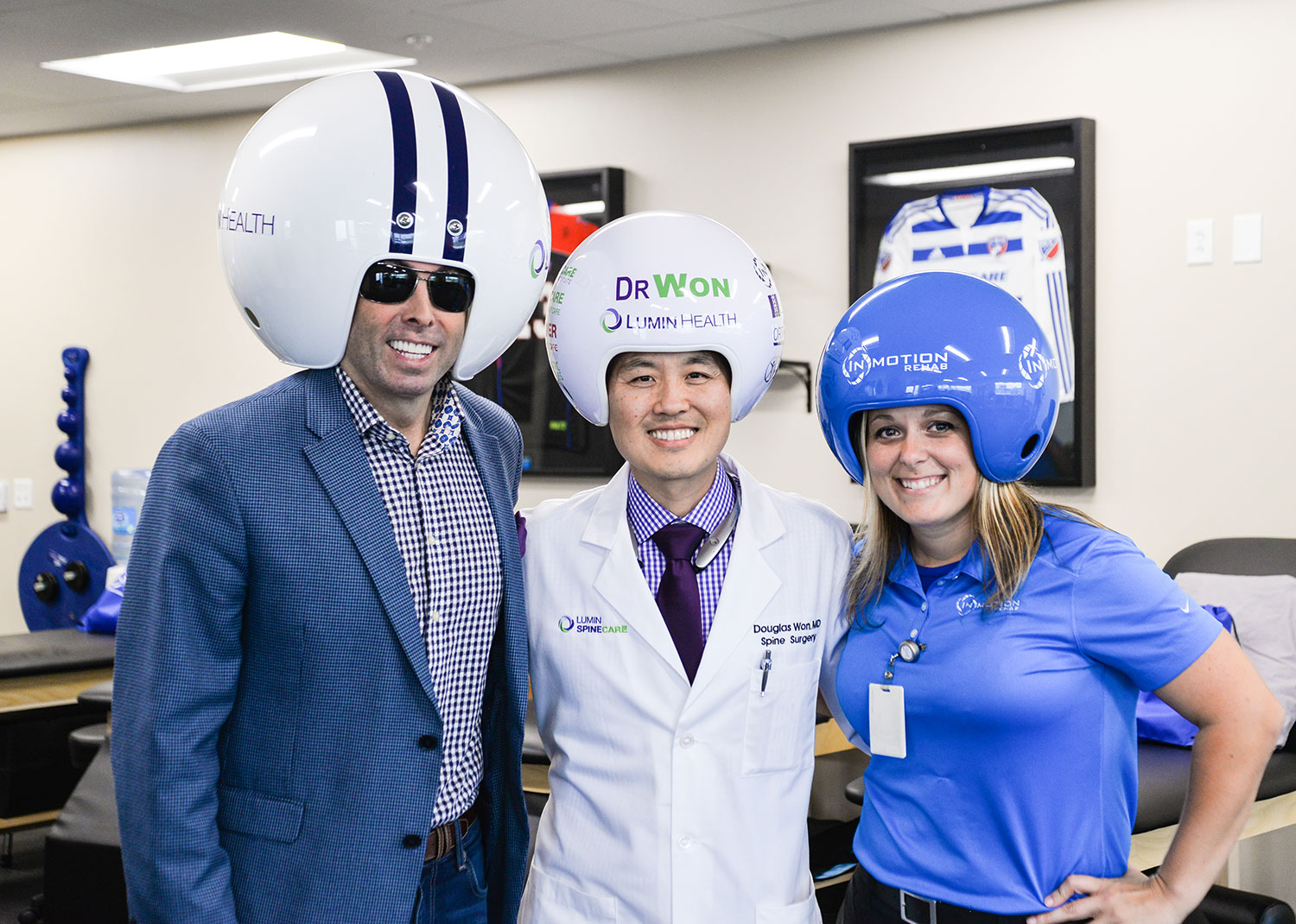"Spine surgeon and CEO of Lumin Health, Dr. Douglas Won (center), is pictured with Gregg ""Wreckin' Ball"" Wilson and Michelle Zammit, rehab and durable medical equipment director, in the InMotion Rehab of Lumin Health Center in Plano. Mr. Wilson is the inventor of the customizable Wreckin' Ball Helmets."